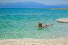 Girl Relaxing In The Water Of Dead Sea