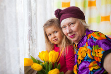 Portrait Of Senior Grandmother With Grandaugther With Yellow Tulips