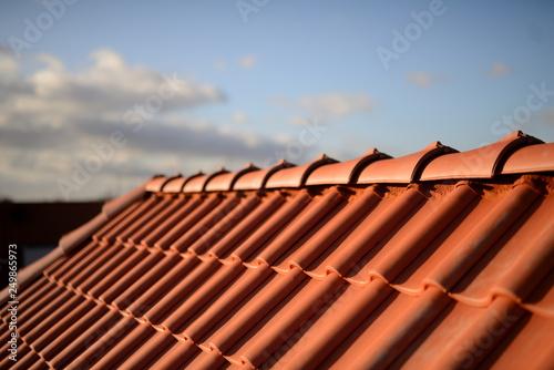Fototapeta Dächer vom Dachdecker mit roten Dachziegeln. Pfannen auf Stadt Haus Neubau mit Abendrot Himmel im Hintergrund. obraz