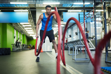 Young athlete in sportswear exercising with ropes while holding their ends during workout in gym
