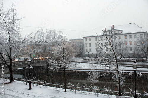 Photo Nevicata in città con traffico alberi e fiume