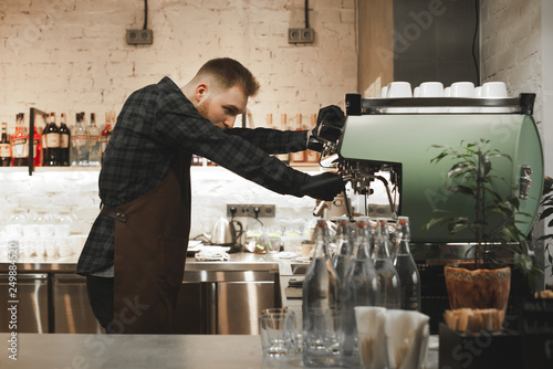 Valokuva  Portrait of bearded concentrated barista preparing cappuccino in a coffee shop