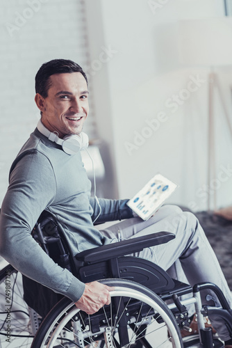 Fotografie, Obraz  Delighted handsome man sitting in the wheelchair