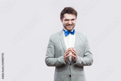 Fotografia Portrait of cunning handsome bearded man in casual grey suit and blue bow tie standing with funny face and palm hand looking at camera with idea