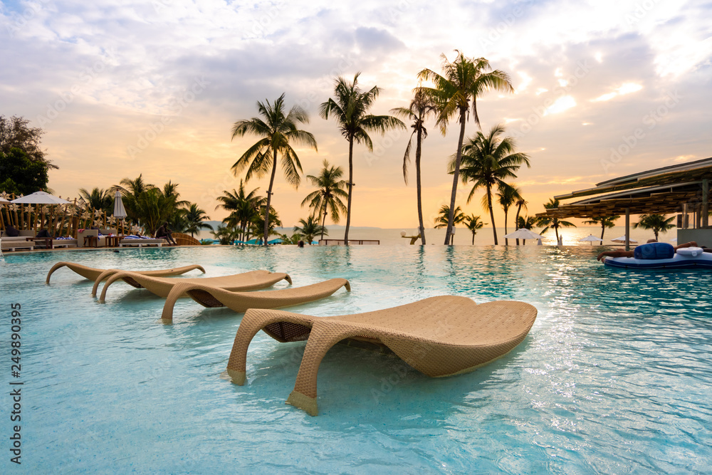 Fototapeta luxury swimming pool on sea view and chair in hotel resort with sunrise time