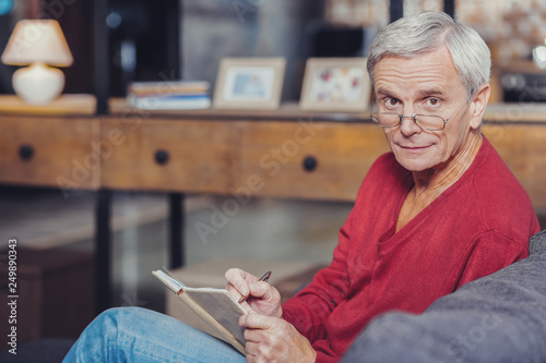 Fotografía  Worried pensioner making notes in his notebook and looking impressed