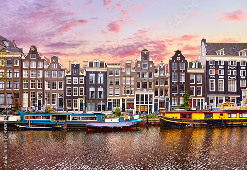 Photo Stands Amsterdam Amsterdam, Netherlands. Floating Houses and houseboats and boats at channels by banks. Traditional dutch dancing houses among trees. Evening autumn street above water pink sunset sky with clouds.