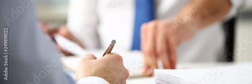 Fotografía  Clerk man at office workplace with silver pen in arms do paperwork closeup