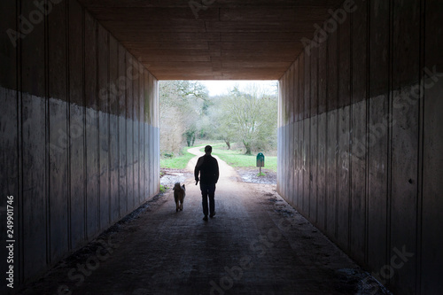 Papiers peints Tunnel A man and his dog walking out of a tunnel into a bright green park