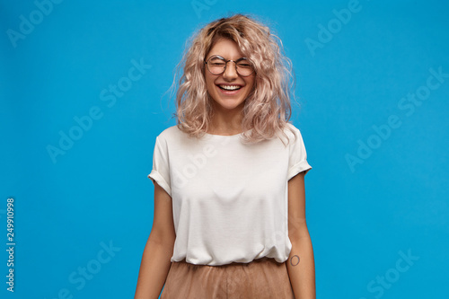 Photographie  Emotional charming young European female in trendy glasses laughing, closing eyes and smiling broadly, showing her white perfect teeth