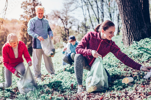 Fényképezés  Beautiful dark-haired woman gathering plastic in forest