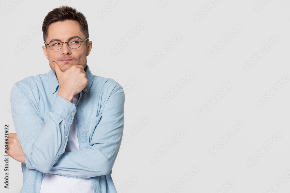 Fototapeta Thoughtful suspicious young man looking aside at copyspace feeling skeptic