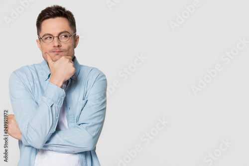 Fotografía  Thoughtful suspicious young man looking aside at copyspace feeling skeptic