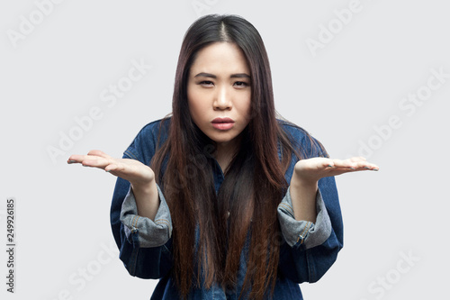 what do you want? Portrait of anger beautiful brunette asian young woman in casual blue denim jacket with makeup standing raised arms and asking Fototapet