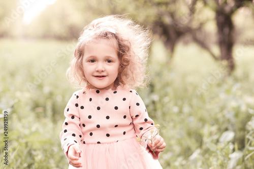 Fotografija  Smiling blonde baby girl 3-4 year old posing outdoors close up