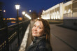 Portrait beautiful young woman in casual clothes walking on evening street. The city embankment of Vologda