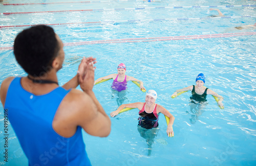 Fototapeta High angle portrait of three mature women doing aqua aerobics in swimming pool with fitness instructor, copy space obraz