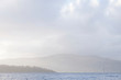 Calm peaceful atmospheric view of lake at Loch Lomond during change of weather from rain to sunshine