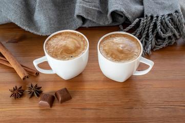Dwie filiżanki kawy z cynamonem, anyżu i czekolady w pobliżu ciepły szalik na drewnianym stole.