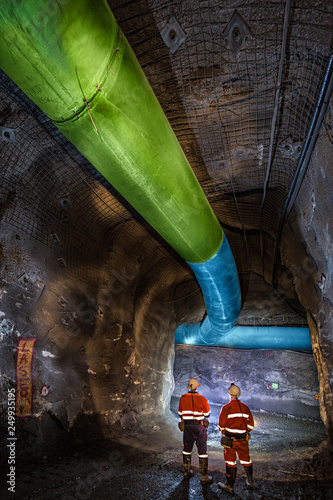 Fotografie, Tablou  Miners inspecting an underground ventilation system in a gold mine in Australia