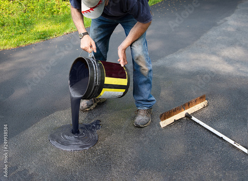 Photo Pouring asphalt onto driveway for resealing