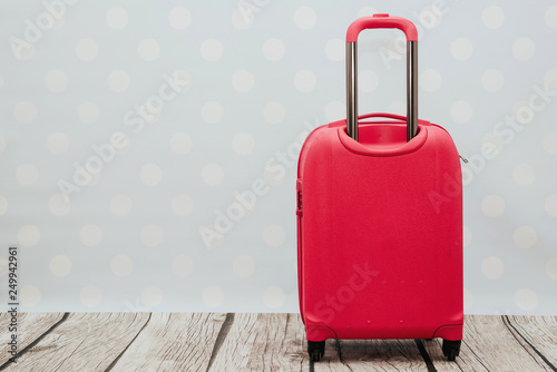 Fototapety, obrazy: A red travel suitcase on wheels, on nice blue pastel  background. Travel concept, packing up before departure. Preparing for travel, going on vacation, break, rest.