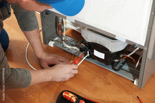 Fotografía  Male technician repairing broken refrigerator indoors, closeup