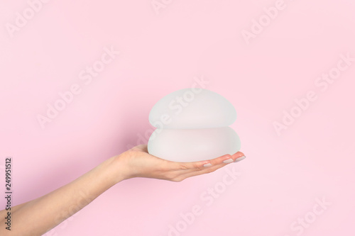 Obraz Woman holding silicone implants for breast augmentation on color background, space for text. Cosmetic surgery - fototapety do salonu