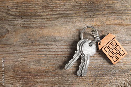 House keys with trinket on wooden background, top view Canvas Print