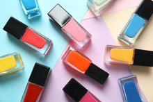 Bottles Of Nail Polish On Color Background, Top View
