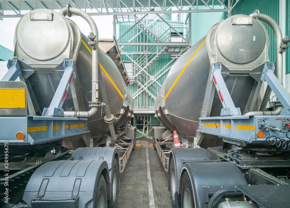 Fototapeta Tanker storage truck loading sugar in storage silo at manufacturing factory. Business industrial concept.
