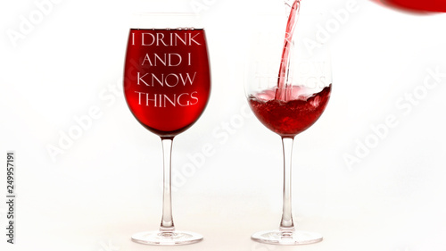 Fotografía Red wine glasses with I drink and I know things text on white background