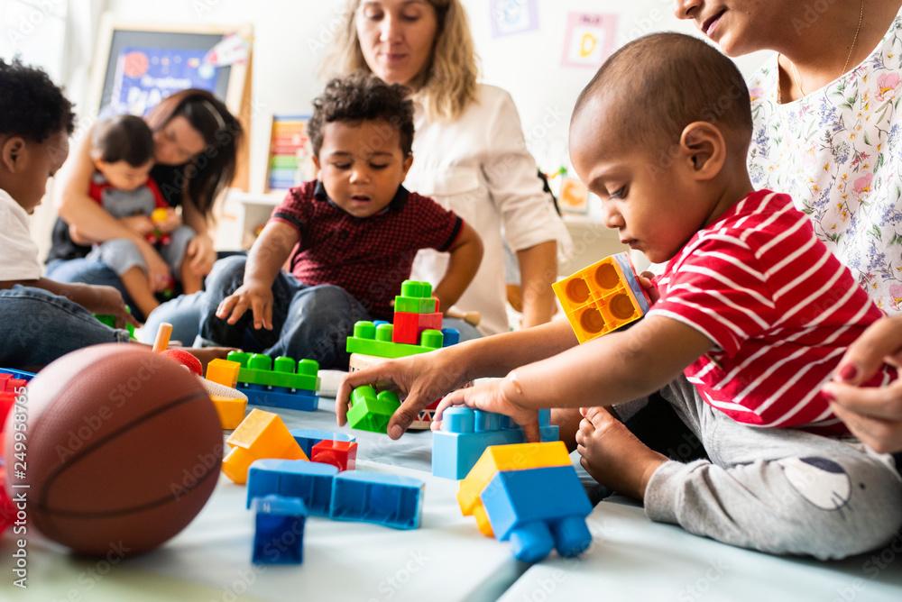 Fototapety, obrazy: Diverse children enjoying playing with toys