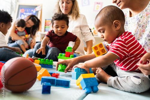 Fotografiet  Diverse children enjoying playing with toys