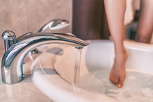 Water Running Bath Woman Dipping Toes In Hot Bathtub Relaxing Time At Home . Luxury Cozy Lifestyle People.
