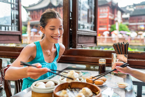 Montage in der Fensternische Shanghai Chinese woman eating at Shanghai restaurant Xiao long bao / xiaolongbao soup dumplings typical food China travel vacation. Asia tourist girl eating Shanghainese steamed dumpling buns with chopsticks.
