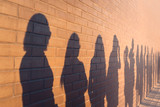 Fototapeta Do przedpokoju - a line of shadows of people lined up against a red brick wall. Stand in a queue to the changes