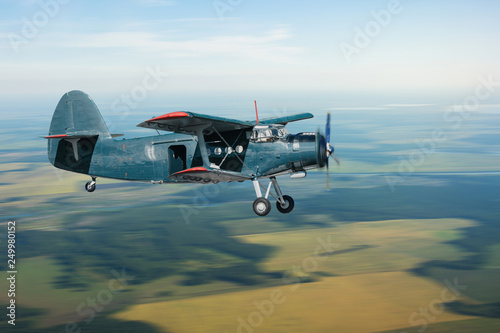 Valokuva  Airplane with a propeller flies on the countryside