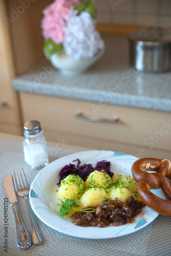 Fotografía  traditional Bavarian German food dumpling with red cabbage and mushrooms is tast
