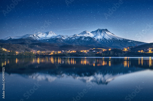 Door stickers Night blue natural background with snow-covered volcano, starry sky with Milky way and reflection in a mountain lake