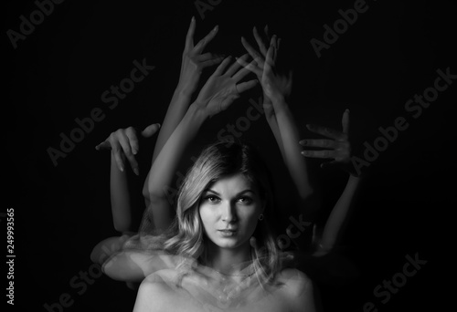 Fotografie, Obraz  Stroboscopic photo of young woman with moving hands on dark background