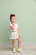 Portrait of cute little girl near color wall