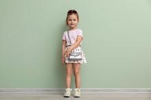 Portrait Of Cute Little Girl Near Color Wall