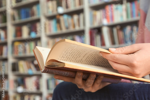 Young woman reading book in library, closeup