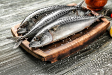 Board With Tasty Raw Mackerel Fish On Wooden Table