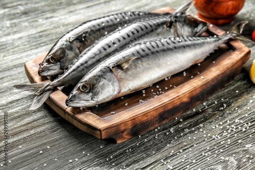 Fotografia  Board with tasty raw mackerel fish on wooden table