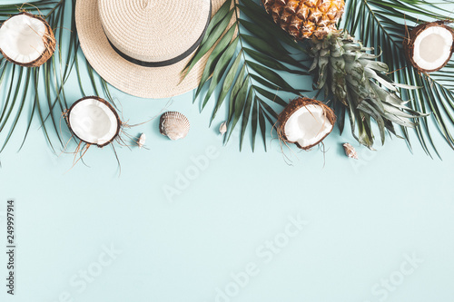 Foto auf Gartenposter Palms Summer composition. Tropical palm leaves, hat, coconut, pineapple on pastel blue background. Summer concept. Flat lay, top view, copy space