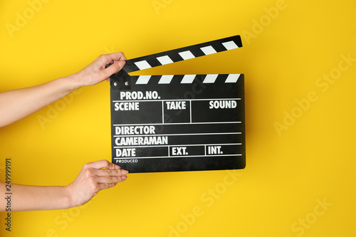 Tableau sur Toile Female hands with cinema clapperboard on color background