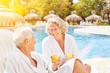 Leinwandbild Motiv Paar Senioren mit Orangensaft im Wellness Urlaub