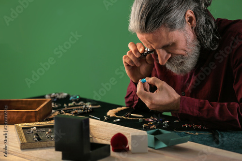 Leinwand Poster  Jeweller examining adornment in workshop
